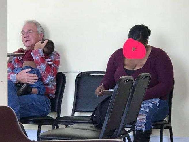 La foto che commuove il web: anziano che culla il bambino